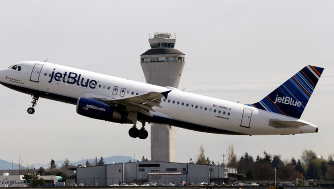 A JetBlue plane departs in view of the air traffic control tower at Seattle-Tacoma International Airport on Tuesday.