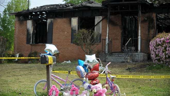 A small memorial is seen in front of a home that was the scene of a fatal house fire in Newnan, Ga., on Saturday.