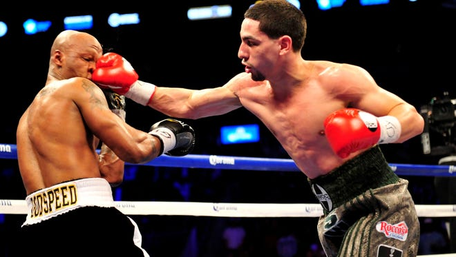 Danny Garcia, right, lands a punch on the nose of Zab Judah Saturday night in Brooklyn. Garcia won via unanimous decision to retain his 140-pound titles.