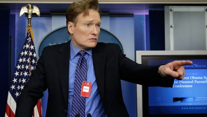 Conan O'Brien poses for photos behind the lectern in the White House briefing room while touring the White House Friday.