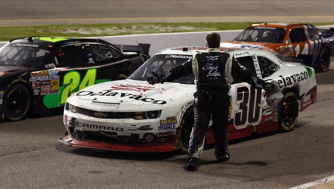 A crew member for Brian Scott, driver of the No. 2 Shore Lodge Chevrolet, confronts Nelson Piquet Jr., driver of the No. 30 Delavaco Chevrolet, on pit road after the NASCAR Nationwide Series ToyotaCare 250 at Richmond International Raceway.