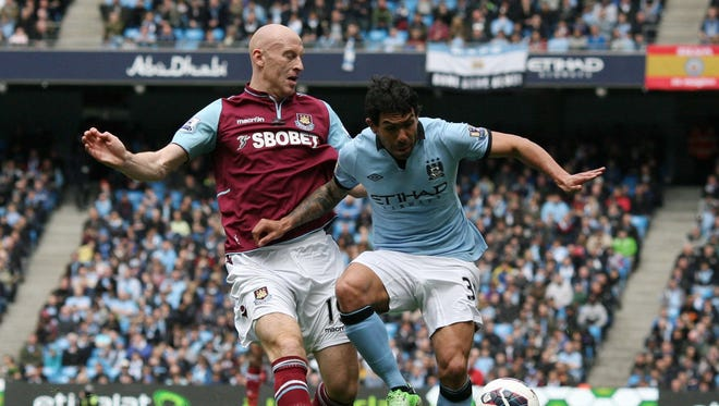 Manchester City striker Carlos Tevez  tackles West Ham United defender James Collins during the English Premier League football match between Manchester City and West Ham United.