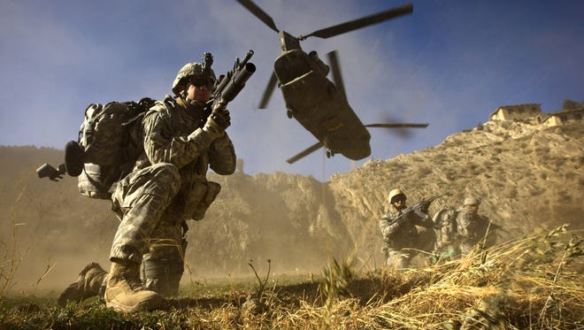 U.S. and Afghan soldiers take up positions after racing off the back of a helicopter in Khost province, along the Afghan-Pakistan border.