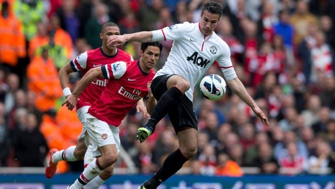 Manchester United's Dutch striker Robin van Persie (right) controls the ball in front of Arsenal's Spanish midfielder Mikel Arteta (L) during the English Premier League at The Emirates Stadium in north London on Sunday.