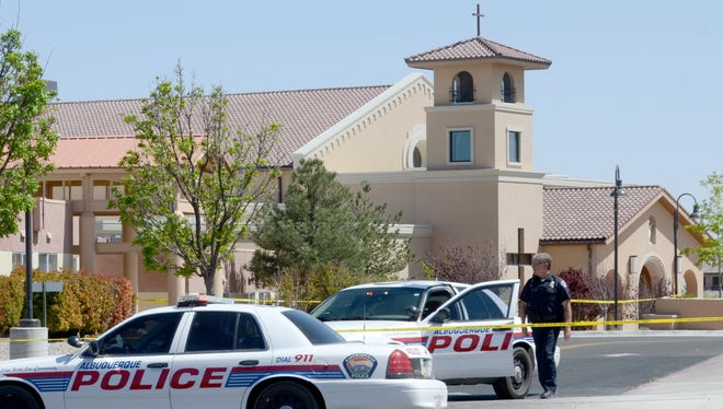 A police officer walks behind tape at St. Jude Thaddeus Catholic Church on Sunday in Albuquerque, N.M.