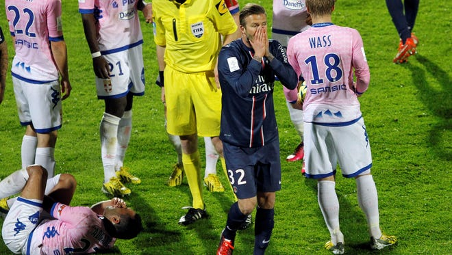 Paris Saint Germain's David Beckham, center, reacts as he leaves the field after the referee showed him a red card during their French League One soccer match against Evian, in Annecy, French Alps, Sunday.