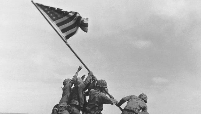 U.S. Marines raising the American flag atop Mt. Suribachi in Iwo Jima, Japan, in 1945.
