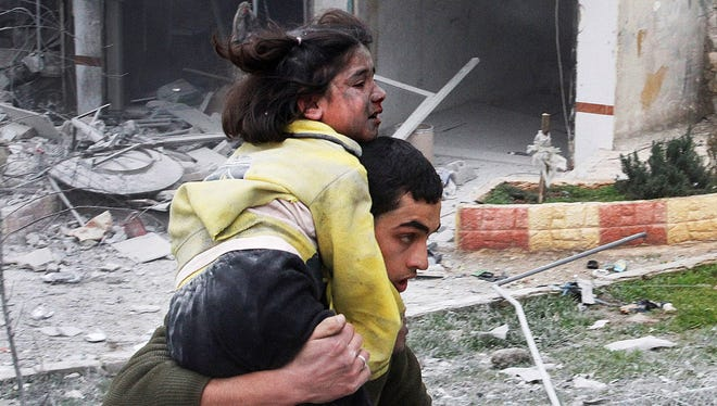 A Syrian carries his sister wounded in a government airstrike in Aleppo in February. The 2-year-old civil war has killed up to 800,000.