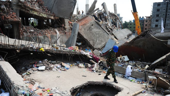A Bangladeshi army member looks into a hole made to recover victims in the rubble.