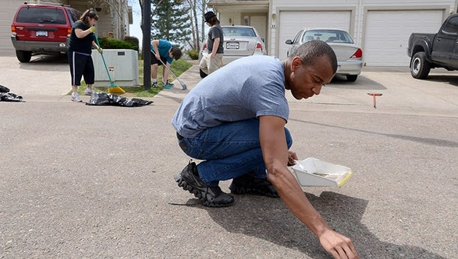 Xavier Farley gathers small pieces of glass from the street on Sunday, April 28, 2013, as he helps clean up the last remnants of a party in the Summerhill neighborhood of Fort Collins, Colo. Farley, who is a Colorado State University student and a resident of the neighborhood, said that at first the party was fun, but it got scary when people started lashing out at the police and climbing poles and cars. Behind Farley, Tracy Kelley and her sons, Caden and Cayce, helped clean up although they do not live in the area and were not at the party.