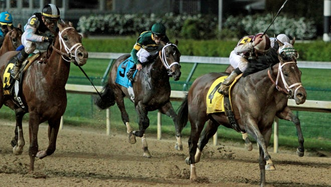 Jockey Joel Rosario and Forty Tales hold off the late charge by stablemate Capo Bastone, far left, to win the Derby Trial horse race on  Saturday night at Churchill Downs