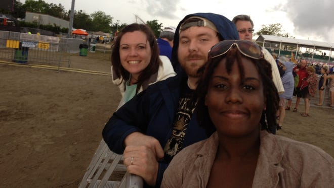 Amy McMinn, left, her husband,  Adam McMinn of Meridian, Miss., and Victoria Downs of New Orleans wait in front of the Acura stage for the Sunday afternoon headliner Dave Matthews Band.