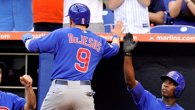 Chicago Cubs right fielder David DeJesus is greeted by  left fielder Alfonso Soriano after DeJesus scores a run on a passed ball in the first inning against the Miami Marlins at Marlins Park.
