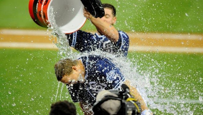 San Diego Padres catcher Nick Hundley is dumped with water by first baseman Yonder Alonso after the game-winning hit during the 12th inning against the San Francisco Giants at Petco Park.