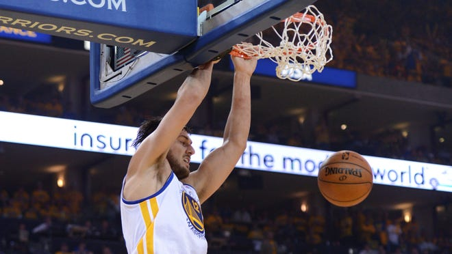 Andrew Bogut dunks on Wilson Chandler during the Golden State Warriors' Sunday game against the Denver Nuggets.