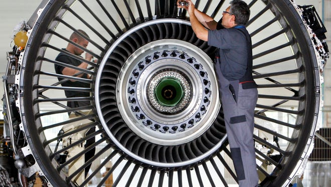 Jet engine mechanics Kay Truemmer, left, and Tobias Zimmermann, right, mount a jet engine in the N3 Engine Overhaul Services, a joint venture set up in Thuringia by Lufthansa Technik AG and Rolls-Royce, in Arnstadt, Germany.