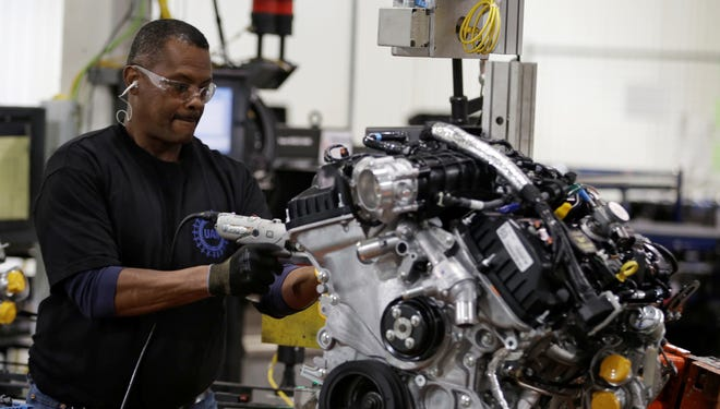 Assembler William Raymond works on the turbo EcoBoost V-6 engine at the Ford Cleveland Engine Plant in Brook Park, Ohio.