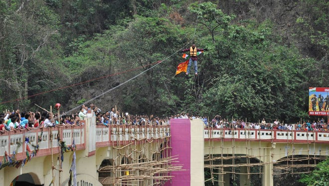 People watch as Sailendra Nath Roy attempts to cross the Teesta River suspended from a zip wire attached to his ponytail moments before his death in Siliguri, West Bengal state, India, on April 28.