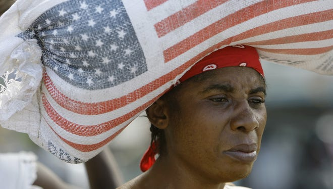 A woman carries a bag containing rice donated by the U.S. Agency for International Development, USAID, as she walks through a market in Leogane, Haiti.
