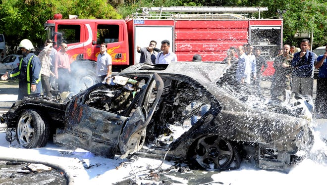 Syrian firefighters extinguish burning cars after a car bomb exploded in Damascus.  State-run Syrian TV says the country's prime minister escaped an assassination attempt when a bomb went off near his convoy.