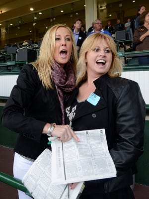 Krista O'Donnell, right, and Ann Marie Tejcek watch as their horse races for the finish line Saturday, April 27, 2013, on the opening night of the spring meet at Churchill Downs. The track has seen crowds grow by switching to night racing for the opening of meets.