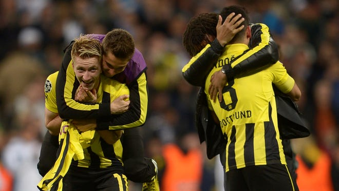 Dortmund's striker Marco Reus (left) celebrates with his teammates at the end of the UEFA Champions League semi-final second leg match against Real Madrid  at the Santiago Bernabeu stadium in Madrid on Tuesday.