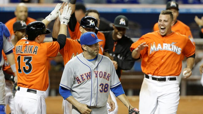 New York Mets relief pitcher Shaun Marcum (38) walks off the field as Miami Marlins' Chris Valaika (13) celebrates with his teammates after the Marlins defeated the Mets 4-3 in 15 innings.
