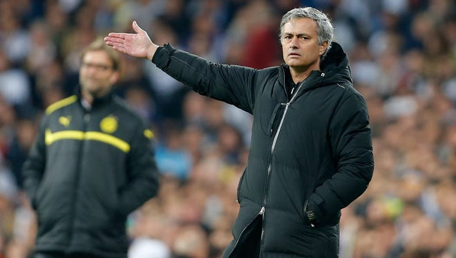 Real Madrid's coach Jose Mourinho gestures, with Dortmund's coach Juergen Klopp in the background, left, during the Champions League semifinal second leg soccer match at the Santiago Bernabeu stadium in Madrid on Tuesdayl.