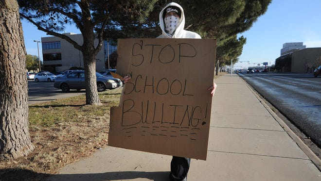 "A man who described himself as a ""disgruntled dad"" walks in front of the Ector County Independent School District administration building on Dec. 9, 2011, in Odessa, Texas."