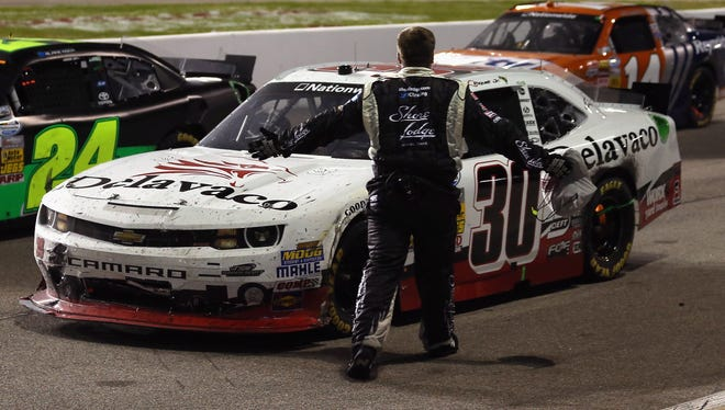 An unidentified crew member for driver Brian Scott (not pictured), approaches driver Nelson Piquet Jr. on pit road after the NASCAR Nationwide Series ToyotaCare 250 at Richmond International Raceway.