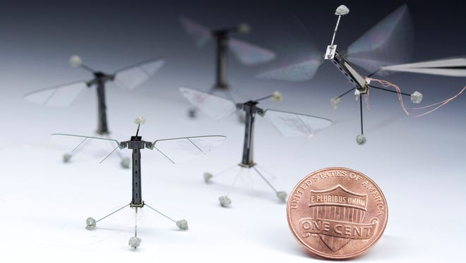 Five individual robotic flies of identical design are shown alongside a U.S. penny for scale.