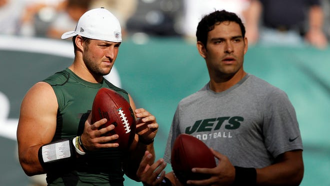 New New York Jets GM John Idzik praised Mark Sanchez, right, for how he has handled the team's confusing quarterback situation, including the past season with Tim Tebow, left.