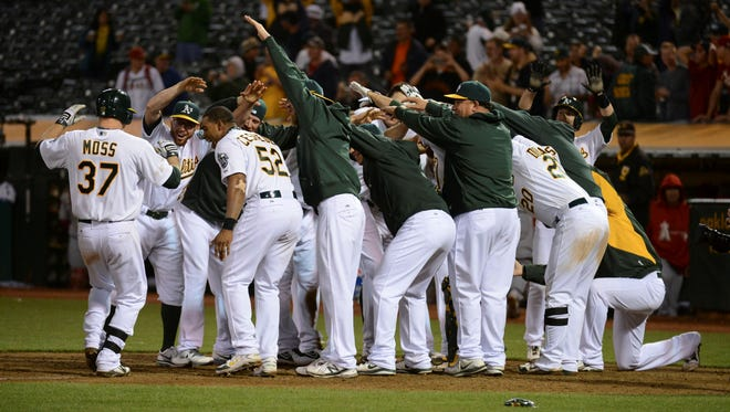 Oakland Athletics first baseman Brandon Moss (37) is congratulated after hitting a walk-off two-run home run against the Los Angeles Angels during the 19th inning at O.co Coliseum. The Athletics defeated the Angels 10-8.