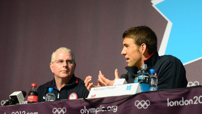 In a file photo from July 26, 2012,  Michael Phelps (right) speaks as his coach Bob Bowman looks on during a press conference at the London Olympics.
