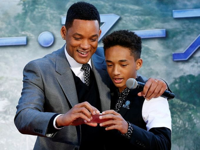 Will Smith and his son, Jaden, take a photograph while promoting their film.