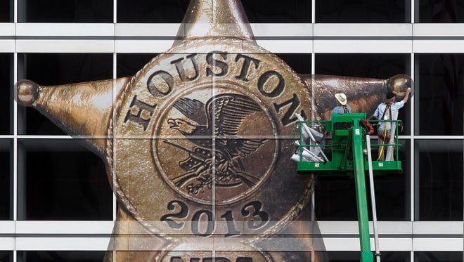 The National Rifle Association logo is placed on the George R. Brown Convention Center by Lynn Creel, left, and Don Reynolds of Display Graphics on Wednesday, May 1, 2013, in Houston.  The 2013 NRA Annual Meetings and Exhibits is scheduled to being Friday. (AP Photo/Houston Chronicle, Johnny Hanson) ORG XMIT: TXHOU301