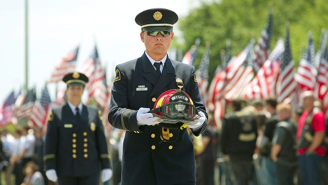 A Dallas Fire Department firefighter carries the helmet of a fallen captain who perished in the West, Texas, explosion during a memorial service in Waco, Texas, on April 25.
