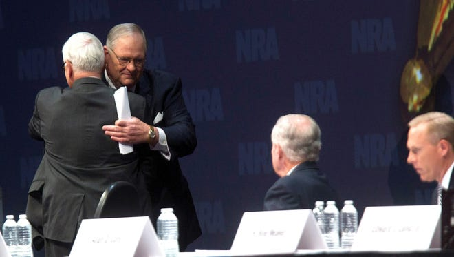 NRA President David Keene, left, says he'll hand the baton to James Porter when the NRA elects a new president Monday. The two hugged during the NRA Annual Meeting of Members Saturday in Houston.