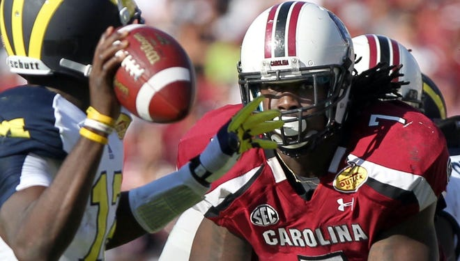 South Carolina defensive end Jadeveon Clowney, putting the heat on Michigan quarterback Devin Gardner in last season's Outback Bowl, will highlight the opening TV game of the college football season Aug. 29 vs. North Carolina..