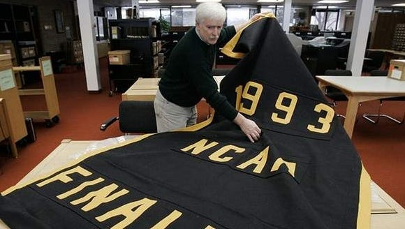 Greg Kinney, archivist at the University of Michigan Bentley Historical Library, unrolls the 1993 NCAA tournament finalist banner being kept in storage in Ann Arbor on Feb. 6, 2007.