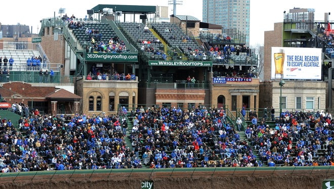 Owners of buildings with rooftop clubs that overlook Wrigley Field say planned outfield video boards would block views and could lead them into bankruptcy.