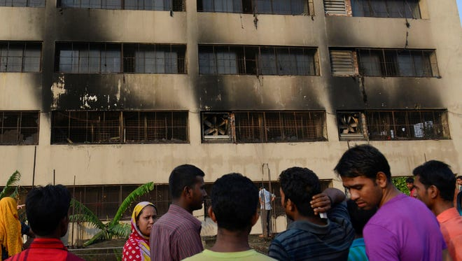 Workers stand outside an 11-story building that houses the Tung Hai Sweater Ltd. factory and apartments.