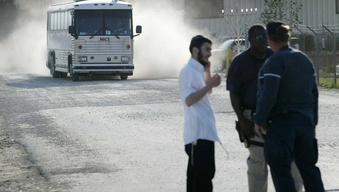 A Homeland Security bus comes rumbles out of the Agriprocessors plant in Postville, Iowa on May 12, 2008. Around 300 workers were arrested at the plant by immigration officials at the kosher slaughterhouse and meat packing plant.