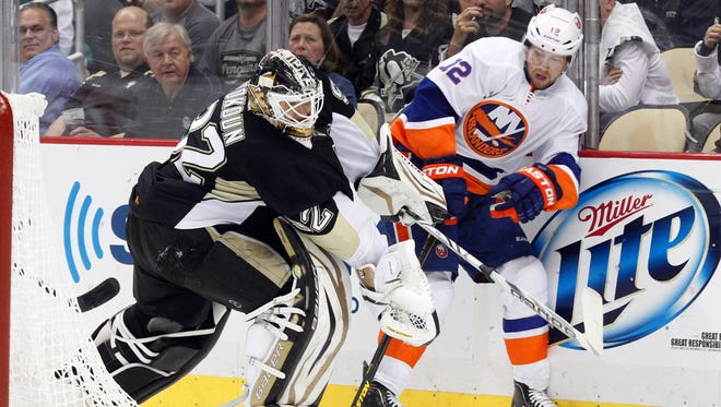 Pittsburgh Penguins goalie Tomas Vokoun (92) and New York Islanders center Josh Bailey (12) battle for the puck behind the net.