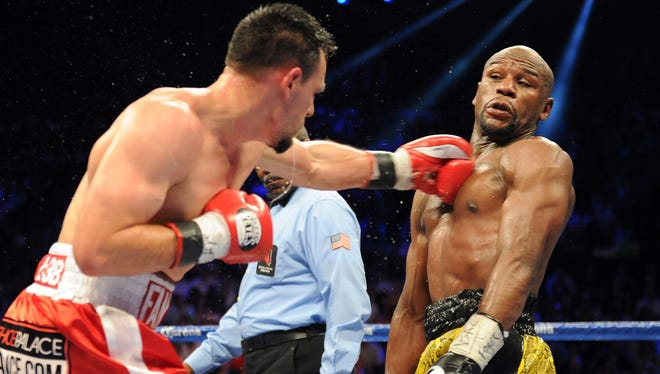 Floyd Mayweather avoids a punch thrown by  Robert Guerrero during their WBC welterweight title fight at the MGM Grand Garden Arena last Saturday. Mayweather won a unanimous decision.