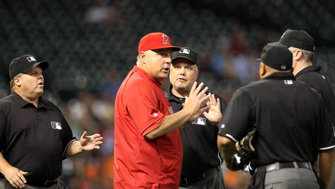 Angels manager Mike Scioscia (14) argues with umpire Fieldin Culbreth (25) and his crew Thursday.