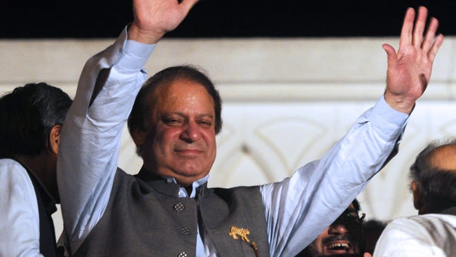 Former Pakistani prime minister and head of the Pakistan Muslim League-N (PML-N) Nawaz Sharif waves to supporters after his party victory in general election in Lahore on Saturday.