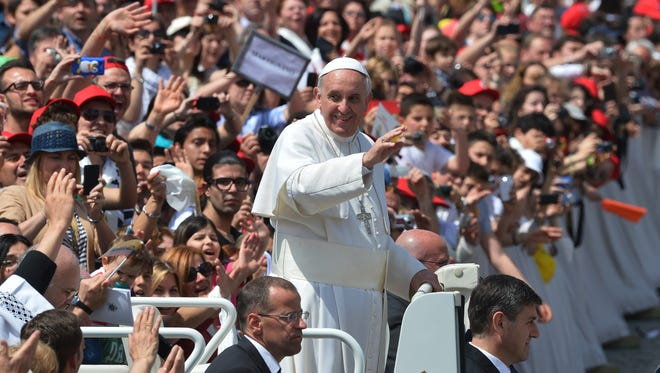 Pope Francis waves to pilgrims Sunday in St. Peter's Square at Vatican at the end of a service canonizing hundreds of saints.