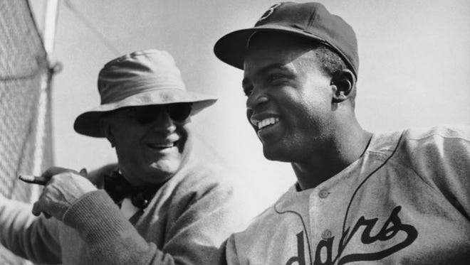Brooklyn Dodgers President Branch Rickey talking to Jackie Robinson in 1949.