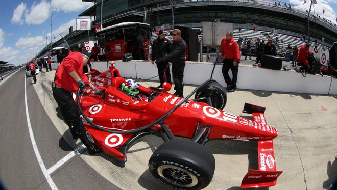Defending Indianpolis 500 winner Dario Franchitti sits in his car while his car is refueled during practice for the 2013 Indianapolis 500 at Indianapolis Motor Speedway.